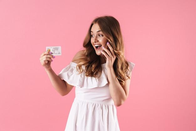 クレジットカードを保持している携帯電話で話しているピンクの壁の上に孤立してポーズをとって幸せな陽気な若いきれいな女性の肖像画。