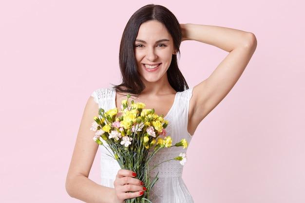 Портрет счастливой веселой молодой женщины в летнем белом платье, держа в одной руке красочные цветы, исправляя ее волосы.