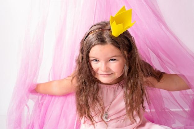 Портрет счастливой детской принцессы, выглядывающей из розового дома