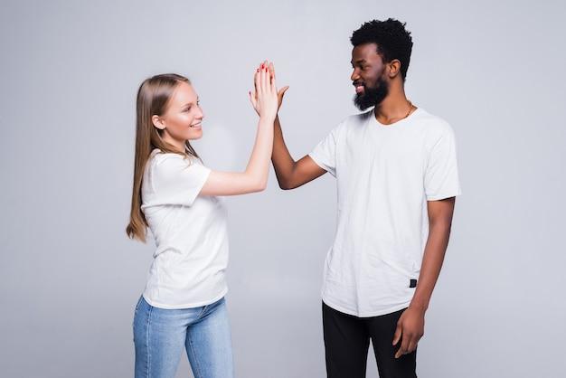 흰 벽 위에 절연 하이 파이브를주는 행복한 커플의 초상화