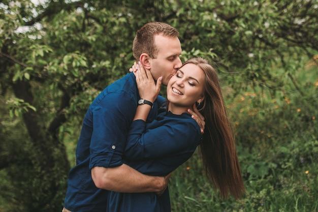 幸せなカップルの肖像画は、春の庭で楽しんでいます。恋をしているカップルの強い家族関係