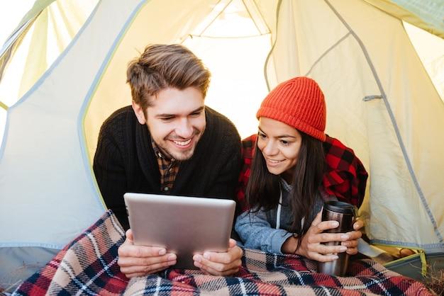テントに横たわって、タブレットコンピューターを一緒に使用して幸せなカップルの肖像画