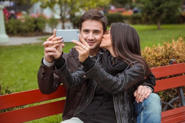 Портрет счастливой пары, делающей селфи на скамейке на открытом воздухе