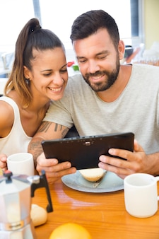 Portrait of a happy couple using digital tablet