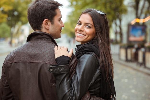屋外を歩いて、正面を振り返って幸せなカップルの肖像画