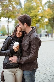 屋外に立っているコーヒーと幸せなカップルの肖像画