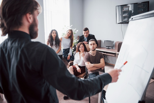 Портрет счастливой творческой группы людей, говорящих в офисе на встрече.