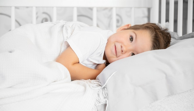 베개와 담요가 있는 흰색 침대에 누워 있는 행복한 귀여운 소년의 초상화. 고품질 사진