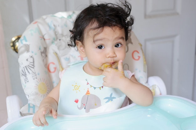 아기 식탁에 앉아 있는 행복한 귀여운 아시아 여자 아기의 초상화, 카메라를 보는 음식으로 얼룩진 입