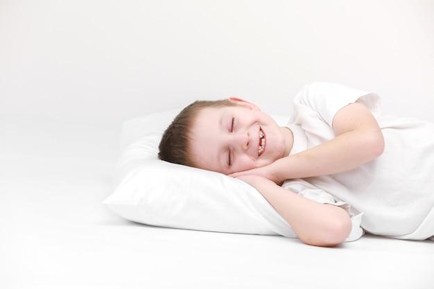 아침에 일어나 흰색 배경에 고립 된 흰색 베개에 누워 행복 귀여운 어린 소년의 초상화. 신선하고 아늑한 침구 시트. 아이들을위한 취침 시간. 행복 한 꿈의 개념입니다.
