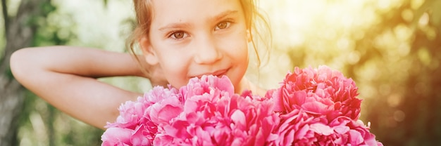 Портрет счастливой милой маленькой кавказской семилетней девочки, держащей в руках букет розовых цветов пиона в полном цвету и выпрямляющей волосы на фоне природы. баннер. вспышка