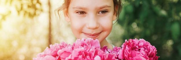 Портрет счастливой милой маленькой кавказской семилетней девочки, держит в руках букет розовых цветов пиона в полном цвету на зеленом фоне природы. баннер. вспышка
