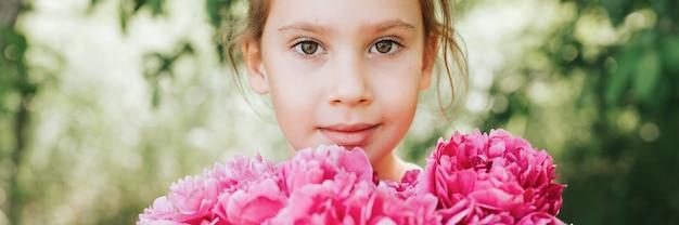 Портрет счастливой милой маленькой кавказской семилетней девочки, держит в руках букет розовых цветов пиона в полном цвету на зеленом фоне природы. знамя