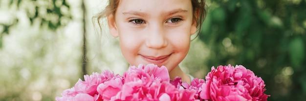 Портрет счастливой милой маленькой кавказской семилетней девочки, держащей в руках букет цветущих розовых пионов на зеленом фоне природы ... баннер