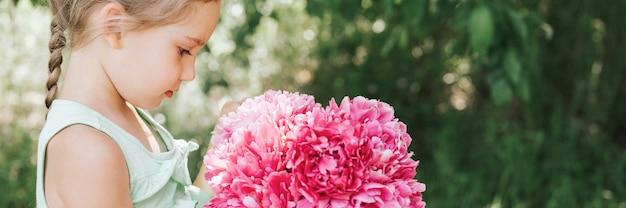 Портрет счастливой милой маленькой кавказской семилетней девочки, держащей в руках и любящей видеть
