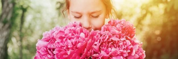 Портрет счастливой милой маленькой кавказской семилетней девочки, держащей в руках и запахом, наслаждающейся букетом розовых цветов пиона в полном цвету на фоне природы. баннер. вспышка