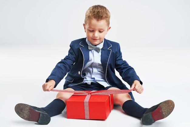 Портрет счастливого милого маленького ребенка, держащего подарочную коробку и смотрящего в камеру, изолированного на сером фоне