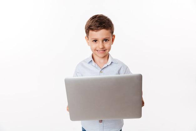 Портрет счастливого милого маленького ребенка держа портативный компьютер