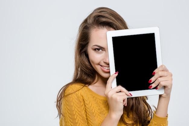 タブレット コンピューターで半分の顔を覆い、白い背景で隔離のカメラを見て幸せなかわいい女性の肖像画
