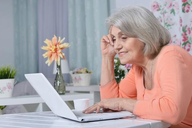 Портрет счастливого пожилого человека с ноутбуком дома