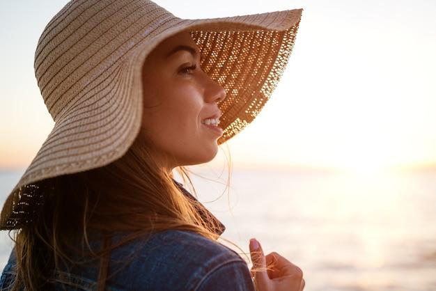 白いデニムのジャケットと海の海岸の麦わら帽子で幸せなエレガントな若い女性の肖像画...