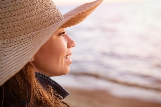 화이트 데님 재킷에 행복 우아한 젊은 여자와 거리 젊은 백인 여성 모델을 찾고 일몰 바다 해안에 밀짚 모자의 초상화는 해변에 가까이