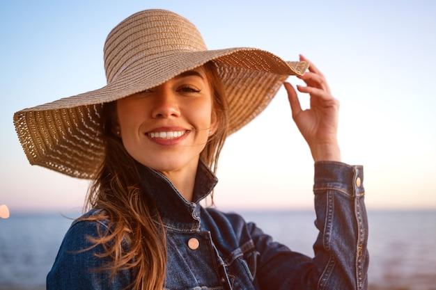 白いデニムのジャケットと夕暮れ時の海岸に麦わら帽子を着て、遠くを見ている幸せなエレガントな若い女性の肖像画