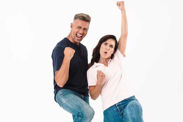 Портрет счастливой эмоциональной взрослой любящей пары делает жест победителя, изолированный над белой стеной
