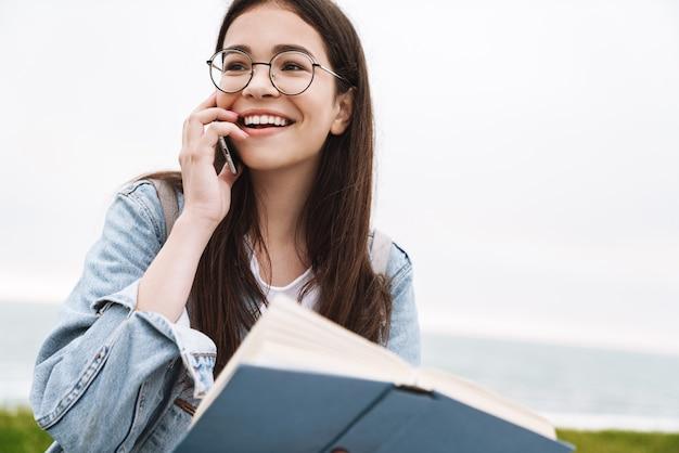 Портрет счастливого эмоционального молодого симпатичного студента женщины в очках гуляет на открытом воздухе, читая книгу, разговаривает по мобильному телефону.