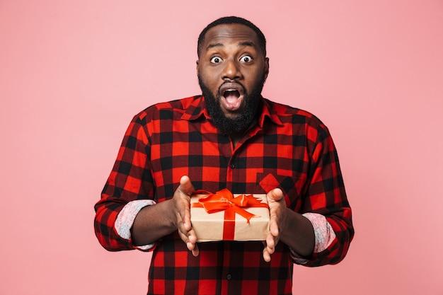Портрет счастливого возбужденного африканского мужчины в рубашке, стоящего изолированно, показывая настоящую коробку