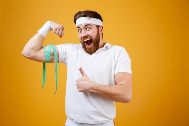 Портрет счастливого возбужденного человека фитнеса измеряя его бицепс