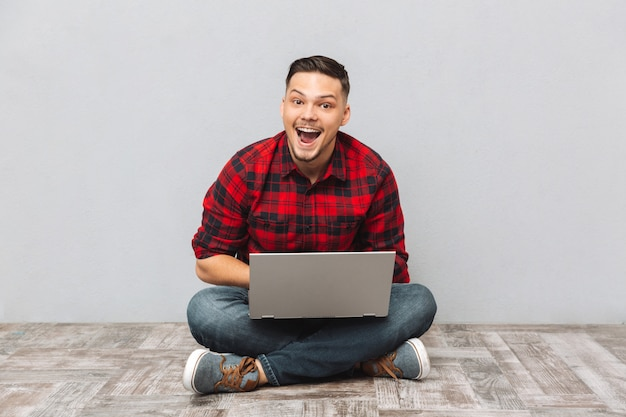 格子縞のシャツの作業で幸せな興奮している男の肖像