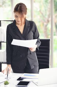 Портрет счастливого руководителя в костюме, работающего на столе в офисе