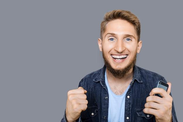 灰色の背景の上に孤立した何かを獲得しているので、カメラの叫び声を見て金髪の髪とひげを持つ幸せな出口の若い男の肖像画。