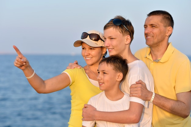 여름에 해변에서 행복한 가족의 초상화, 그의 손으로 가리키는 여자