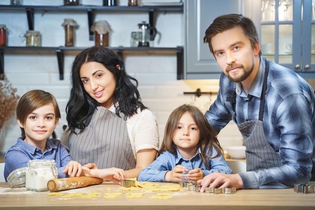 台所でクッキーを調理する幸せな家族の肖像画