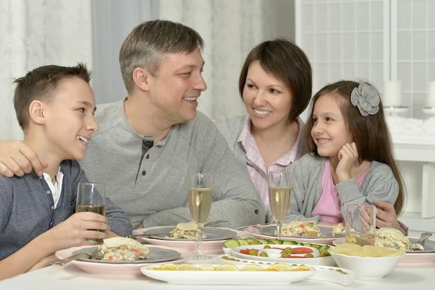 식탁에서 저녁 식사를 하는 행복한 가족의 초상화