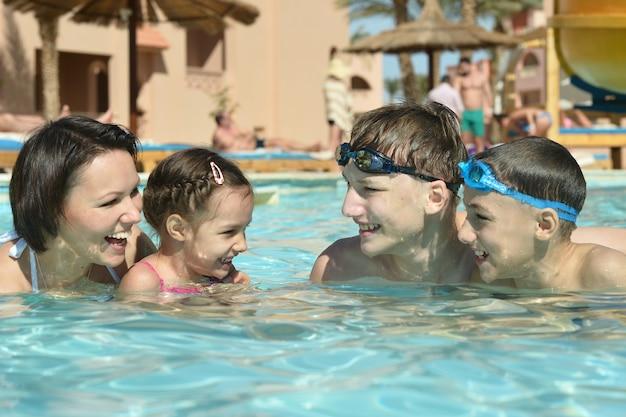 プールで楽しんで幸せな家族の肖像画