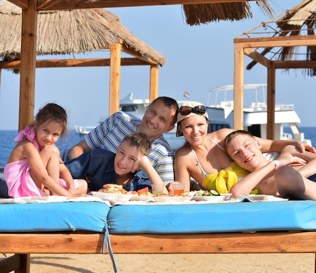 ビーチで昼食をとっている幸せな家族の肖像画