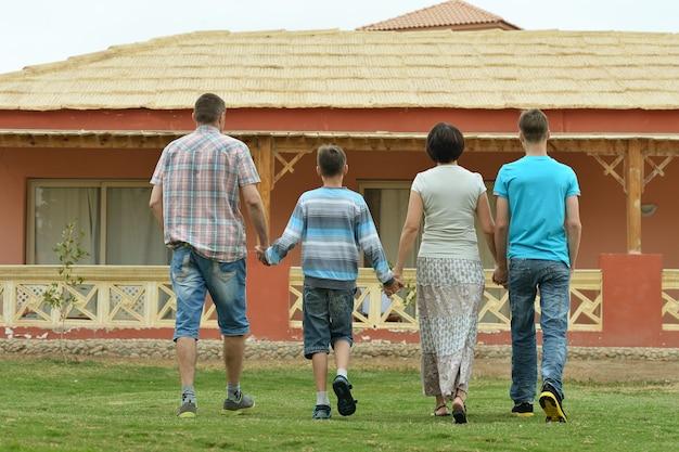 Портрет счастливой семьи в тропическом рессорте, вид сзади