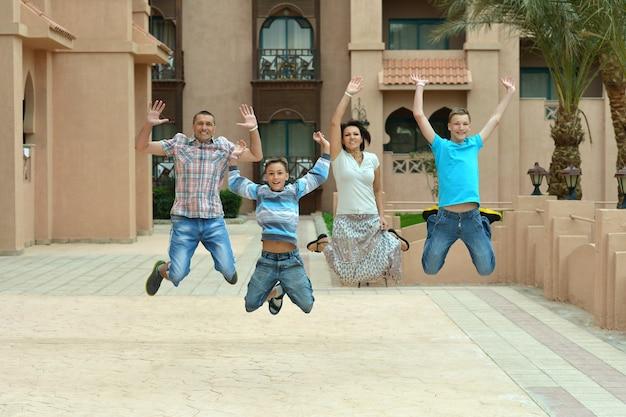 Портрет счастливой семьи, прыгающей на тропическом курорте.