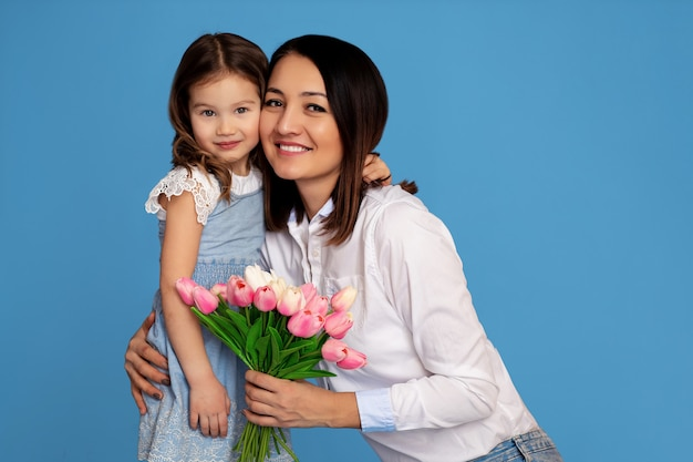 幸せな家族の肖像画。白い歯の笑顔の母と娘が手にピンクのチューリップの花束を握る