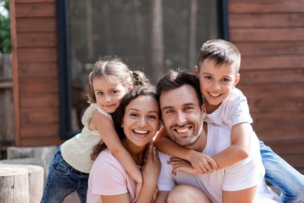 Портрет счастливой семьи из четырех человек, мамы, папы, дочери и сына, дети обнимают родителей, все радуются совместному отдыху жарким летом.