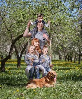 Портрет счастливой семьи на качелях в саду. хорошее время