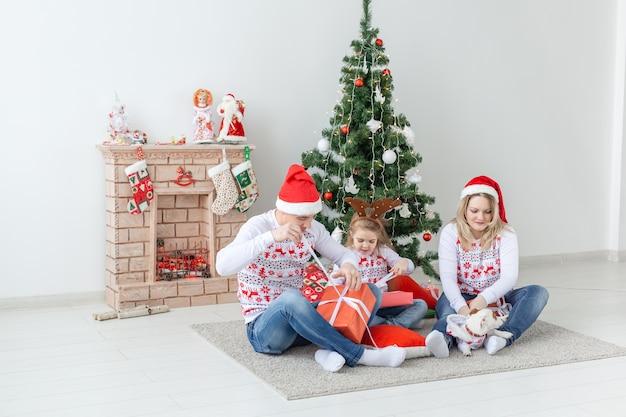 クリスマスの時期に贈り物を開く幸せな家族の肖像画