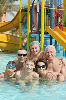幸せな家族の肖像画はプールでリラックス