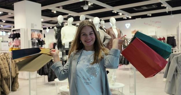 ショッピングバッグを持って衣料品店で笑顔、ダンス、回転する幸せな女性の肖像画。デパートでファッションデザイナーのアイテムを購入する若い大人の白人女性の顧客。