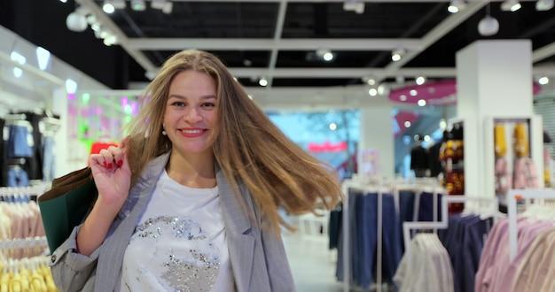 ショッピングバッグを持って衣料品店で笑顔、ダンス、回転する幸せな女性の肖像画。デパートでファッションデザイナーのアイテムを購入する若い白人女性の顧客。
