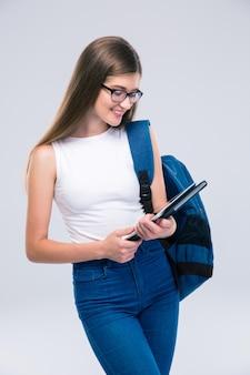 Whtie スペースに分離されたタブレット コンピューターを使用してバックパックを持つ幸せな女性 10 代の若者の肖像