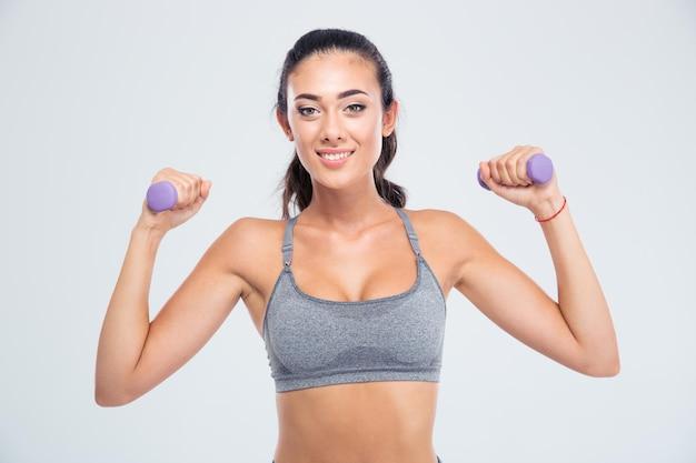 Портрет счастливой фитнес-женщины, работающей с гантелями, изолированной на белой стене